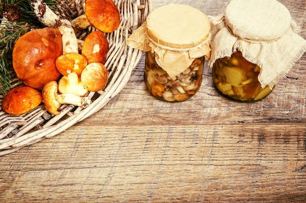 Floresta fresca e cogumelos em conserva em uma jarra sobre um fundo rústico de madeira com temperos, preparo de conservas. efeito matizado