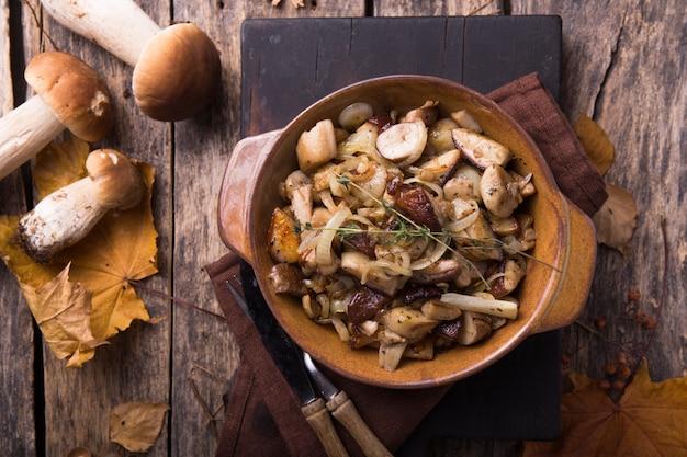 Floresta frita cogumelos, boletos, cebolas. prato rústico em uma frigideira, comida vegetariana de outono em cima da vista