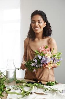 Florista africana bonita alegre que sorri fazendo o ramalhete no local de trabalho sobre a parede branca.