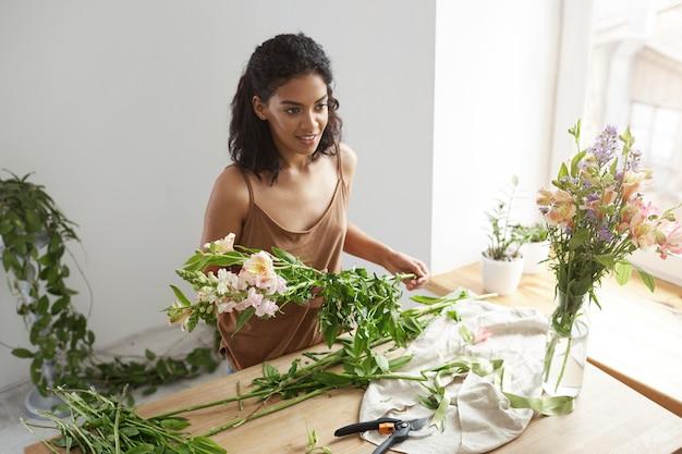 Florista africana bonita nova da mulher que toma das flores no local de trabalho sobre a parede branca.