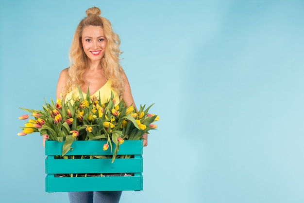 Florista alegre jovem loira com uma caixa de tulipas sobre uma superfície azul com espaço de cópia
