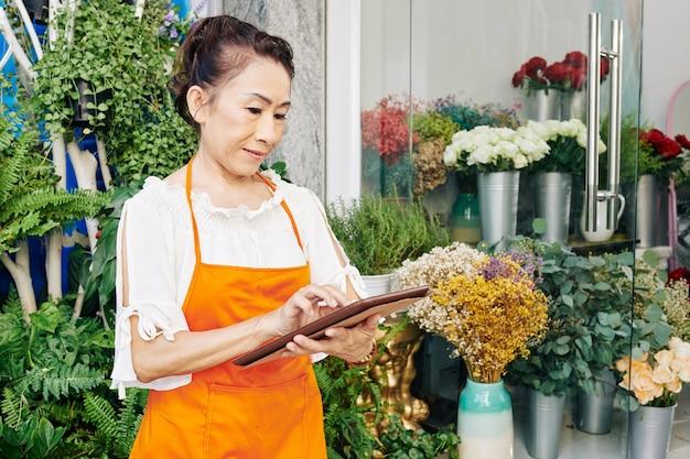 Florista asiática sênior verificando pedidos de clientes no computador tablet