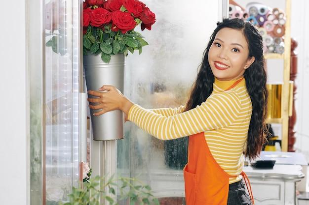 Florista asiática sorridente e atraente tirando um balde de rosas de um mostruário floral