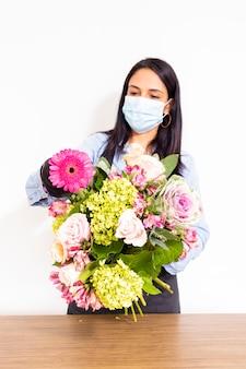 Florista bonito mulher está fazendo um buquê de rosas, hortênsias e alstroemerias