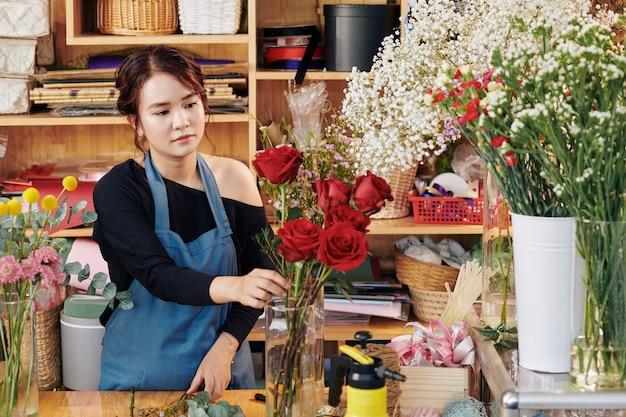 Florista colocando flores no vaso