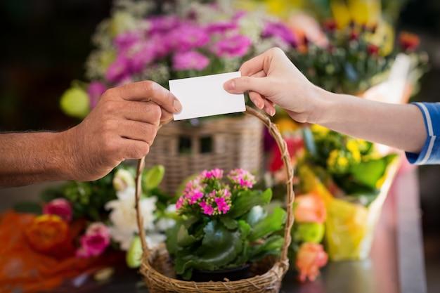 Florista dando cartão de visita ao cliente