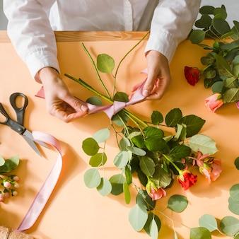 Florista de close-up, fazendo uma fita para buquê