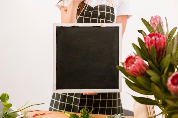 Florista de close-up segurando uma placa preta