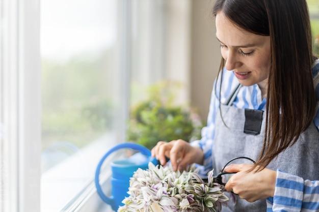 Florista de closeup cortando folhas de begônia cultivada em vasos de plantas em jardim doméstico