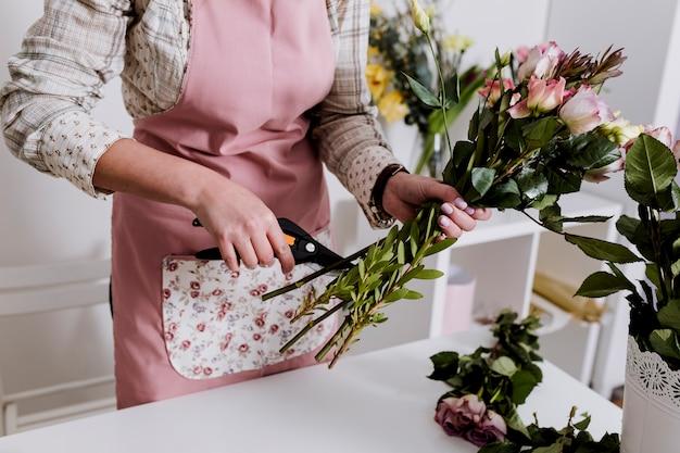 Florista de colheita preparando flores