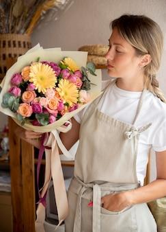Florista de dose média segurando buquê