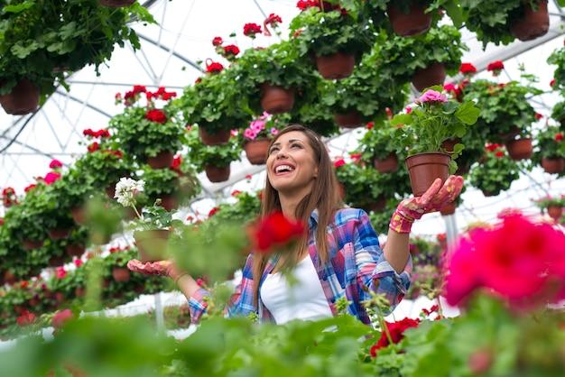 Florista de mulher bonita com sorriso segurando flores em vasos em estufa de viveiro de plantas.