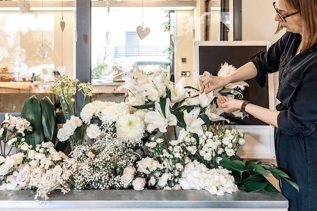 Florista de mulher bonita cuida das flores em sua loja. conceito de empresa de pequeno porte, loja de flores. estilo de vida. vista lateral.