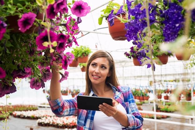 Florista de mulher bonita usando computador tablet na estufa do centro do jardim, verificando a venda de flores