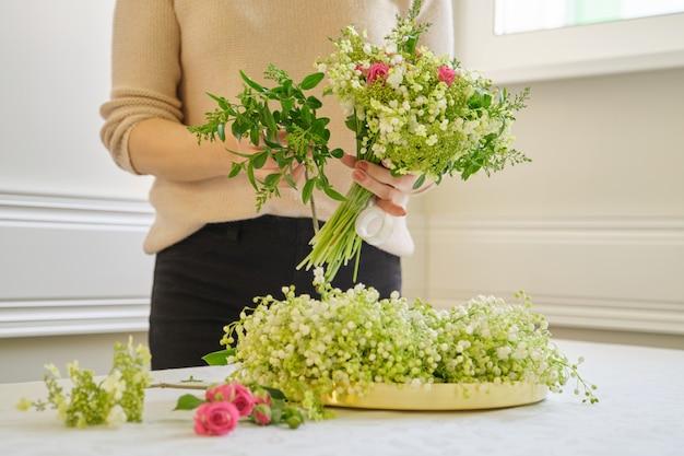 Florista de mulher com diferentes flores na mesa fazendo buquê