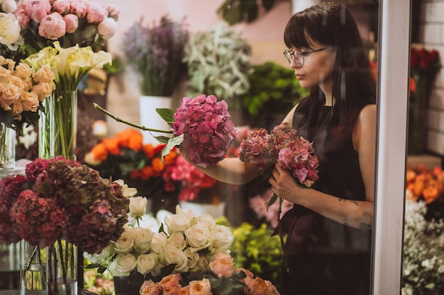 Florista de mulher em sua própria loja floral, cuidando de flores