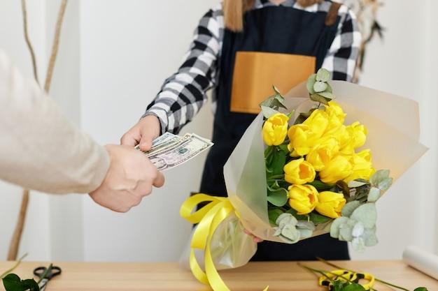 Florista de mulher vendendo flores para um homem. pagamento em dinheiro pela flor
