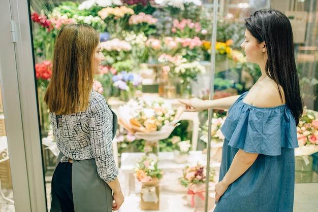 Florista e cliente do sexo feminino escolhe flores para a preparação do buquê. interoir boutique floral com composições frescas