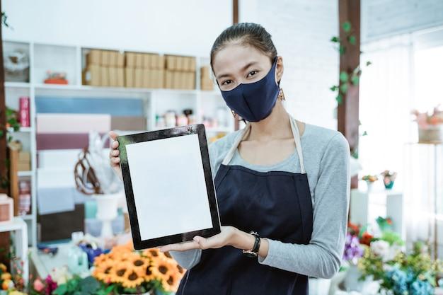 Florista em retrato segurando um tablet e mostrando o pagamento com código de barras qris