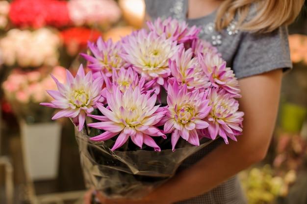 Florista em um vestido cinza, segurando um lindo buquê de flores rosa brilhante