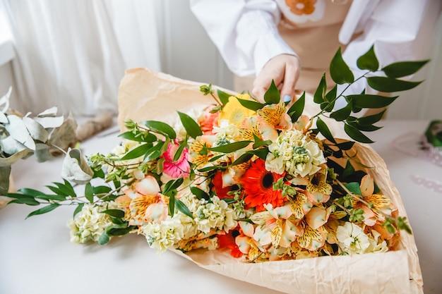 Florista em uma camisa branca embrulhando um buquê de flores coloridas variadas em papel artesanal
