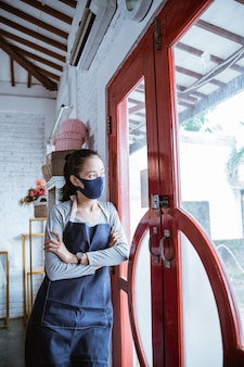 Florista entediante usando avental e máscara se encosta na porta ao amanhecer