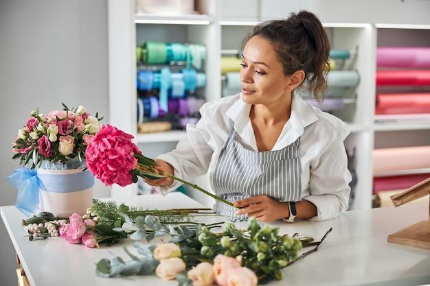 Florista entusiasmada fazendo um buquê de lindas flores