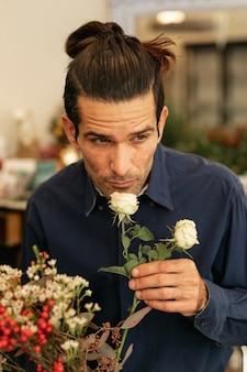 Florista experiente cheirando rosas brancas