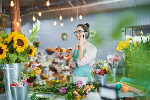 Florista falando por smartphone na loja
