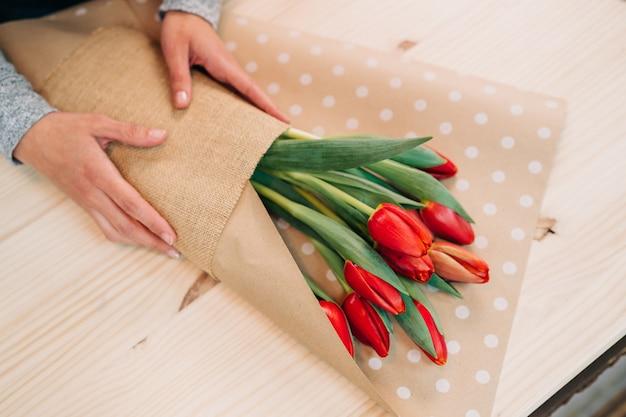 Florista faz buquê de tulipa vermelha e embrulho em papel de pacote na mesa de madeira
