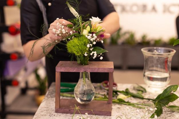 Florista faz um buquê. composição de flores na caixa de madeira