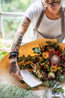 Florista fazendo buquê de arranjo de flores frescas com cartão de feliz aniversário