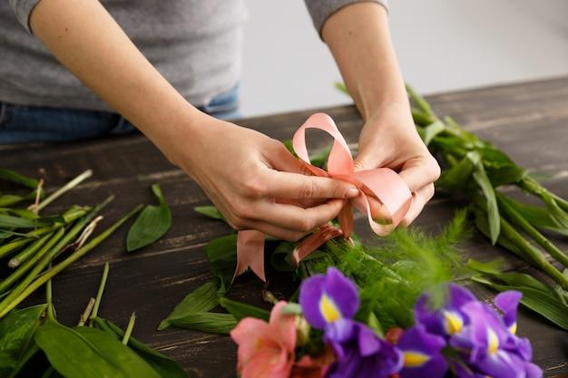 Florista fazendo buquê de flores, aperte a fita