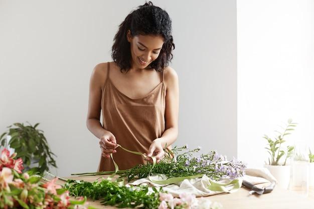 Florista fêmea africana atrativa que sorri guardando a fita verde que trabalha com as flores no local de trabalho sobre a parede branca.