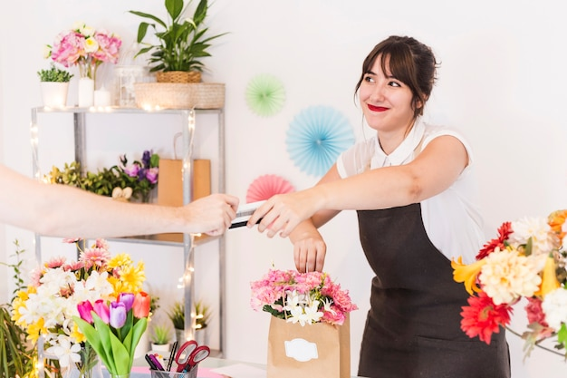 Florista feminina, aceitando cartão de crédito do seu cliente