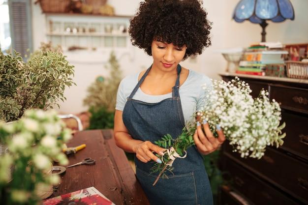 Florista feminina africana, olhando para um monte de flores brancas