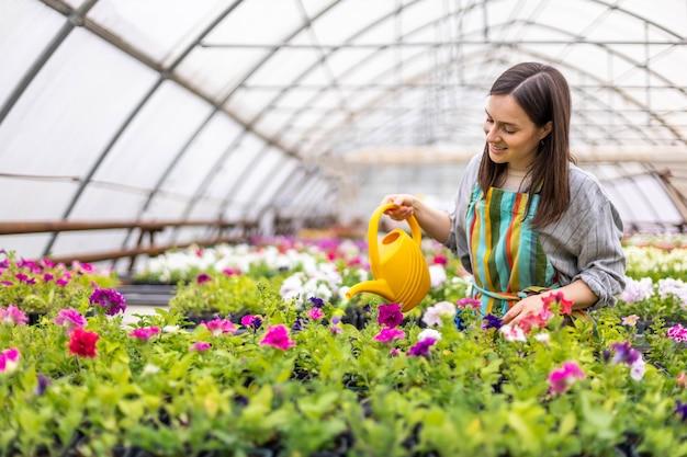 Florista feminina alegre despejando água fresca em um canteiro de flores com folhas multicoloridas e pétalas