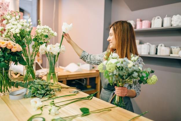 Florista feminina coloca flores em vasos, processo de preparação de buquê fresco.