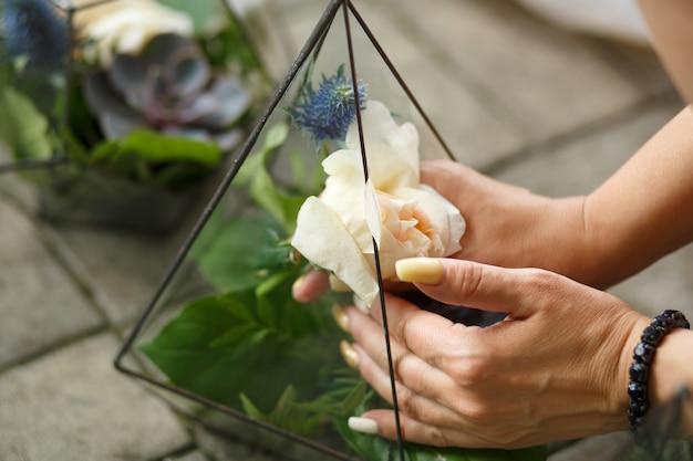 Florista feminina coloca flores frescas de suculentas e rosas no florarium de vidro.