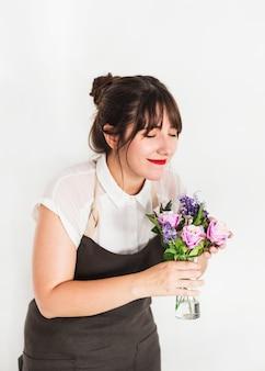 Florista feminina com olhos fechados cheirando flores no vaso