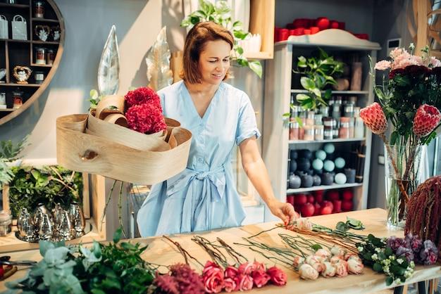Florista feminina decora a composição com casca de bétula em cima da mesa na floricultura.