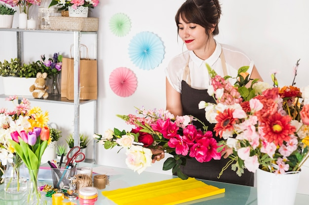 Florista feminina fazendo buquê de flores na loja floral