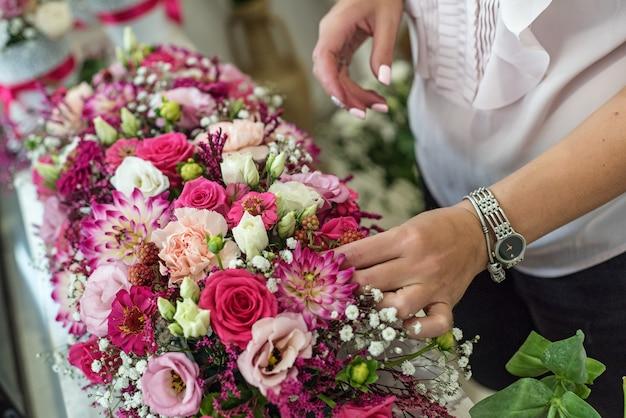 Florista feminina fazendo lindo buquê na loja de flores