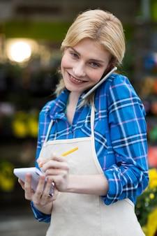 Florista feminina, levando a ordem no celular na loja de flores