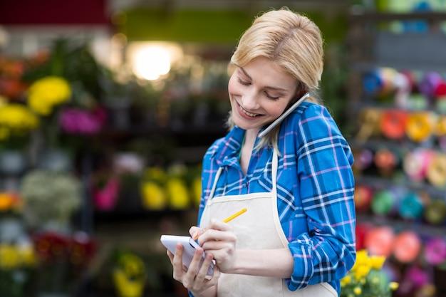 Florista feminina, levando a ordem no celular