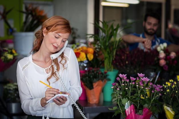 Florista feminina, pegando um pedido no telefone