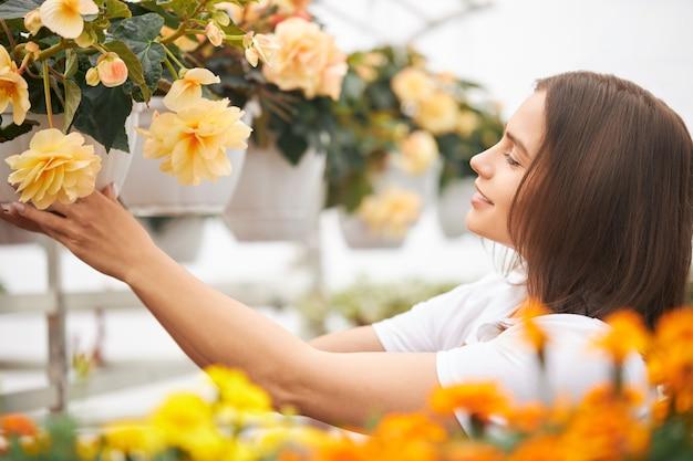 Florista feminina positiva verificando o crescimento das plantas em vasos