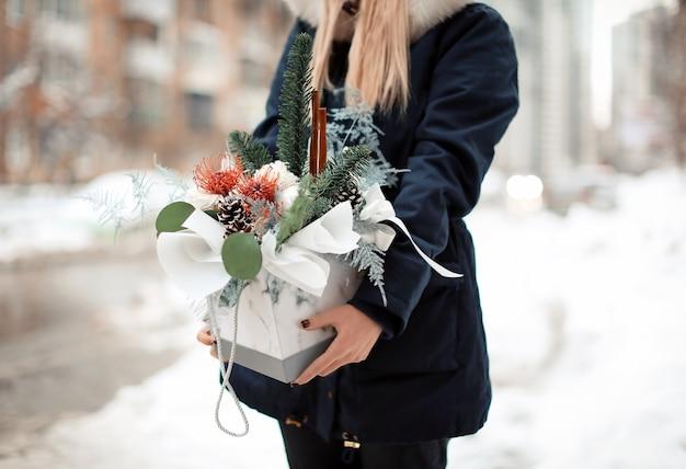 Florista feminina segurando uma composição floral em uma caixa ao ar livre