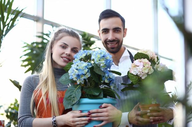 Florista homem e mulher segurando flor hortensia