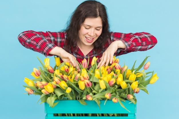 Florista jovem alegre com caixa de tulipas sobre fundo azul